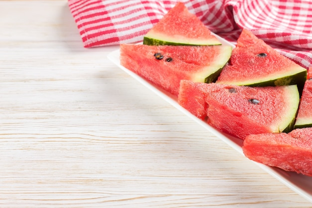 Slices of watermelon on the plate on white wooden background.