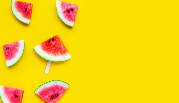 Slices of watermelon on yellow background. top view