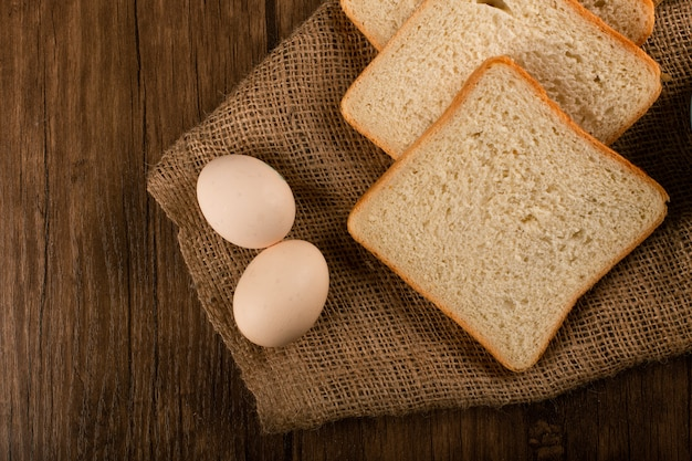 Slices of white bread and eggs on tablecloth