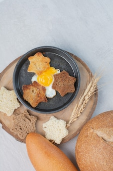 Slices of white and brown breads with fried egg on wooden plate.