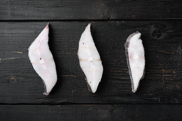 Slices of white fish seafood market set, on black wooden table background, top view flat lay