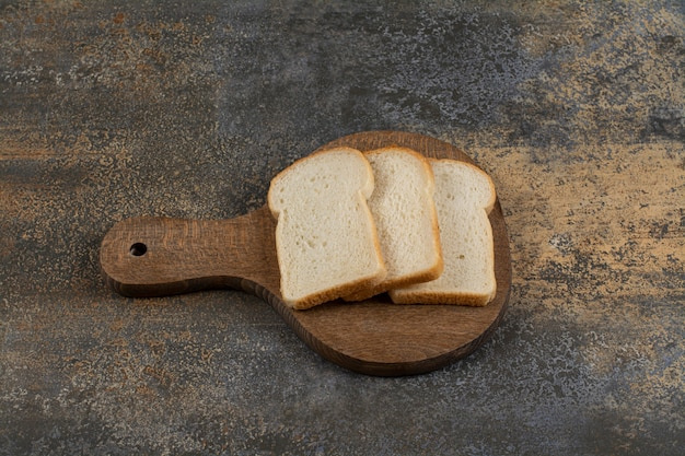 Slices of white toast bread on wooden cutting board