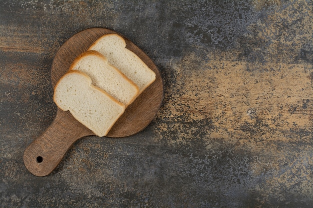 Slices of white toast bread on wooden cutting board.