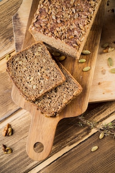 Slices of whole grain brown bread with sunflower seed on chopping board