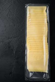 Slices of yellow cheese in sealed pack, on black table