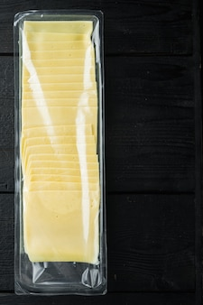 Slices of yellow cheese in sealed pack, on black wooden table with copy space for text