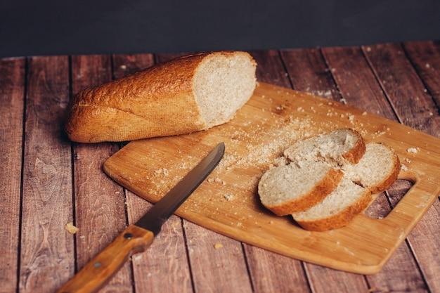 木製のまな板の新鮮な朝食でパンをスライスする