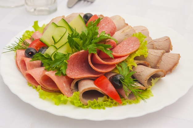 Slicing assorted sausages and meat with vegetables on a white plate