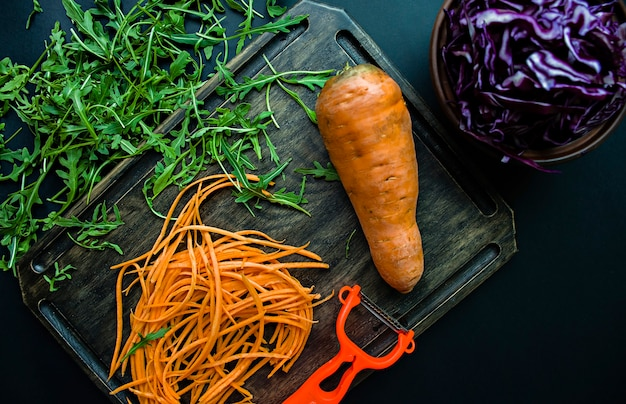 Slicing carrots on an oak board in the surface cutting red cabbage and arugula on a black surface