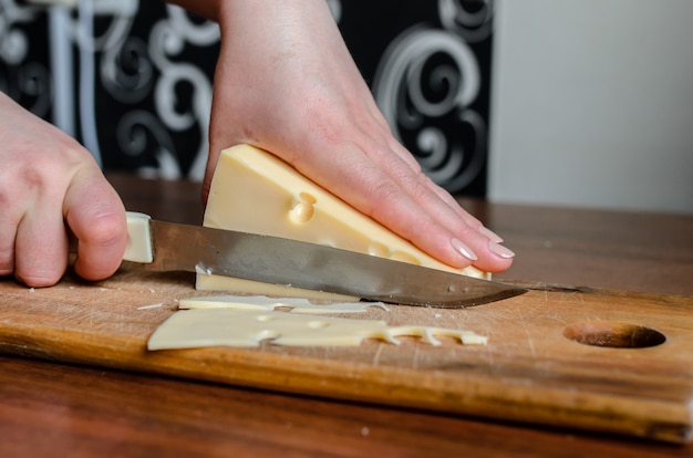 Нарезка сыра на деревянной доске