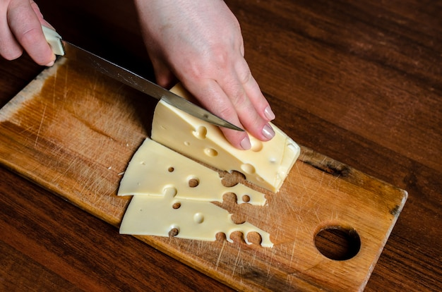Slicing cheese on a wooden board.