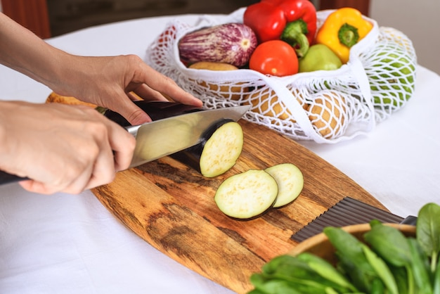 Нарезка баклажанов на деревянной доске с ножом, приготовление вегетарианского ужина крупным планом
