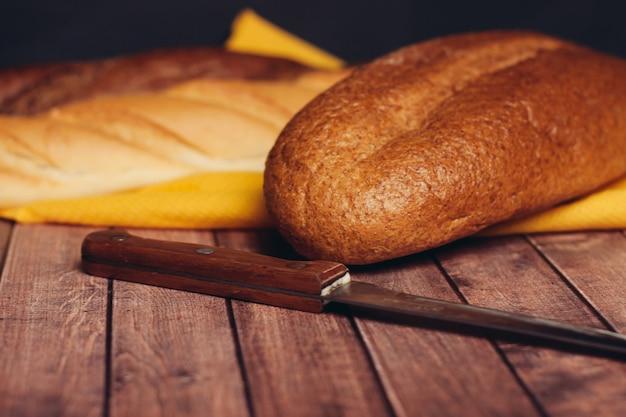 木製のまな板の朝食の食事に焼きたてのパンをスライスする