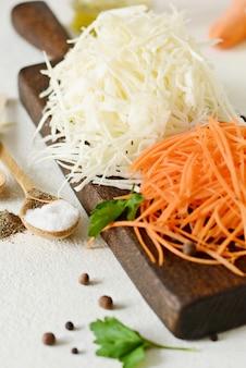 Нарезка свежей капусты и моркови на деревянной доске на светлом фоне