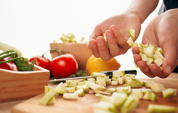 新鮮な野菜をスライスしてテーブルキッチンの健康食品を切る