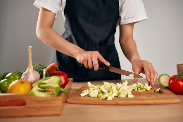 キッチンでサラダの健康食品のために新鮮な野菜の材料をスライスする