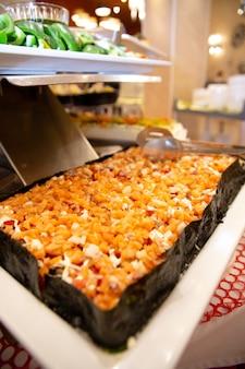 Нарезка филе красной рыбы на шведском столе в отеле.