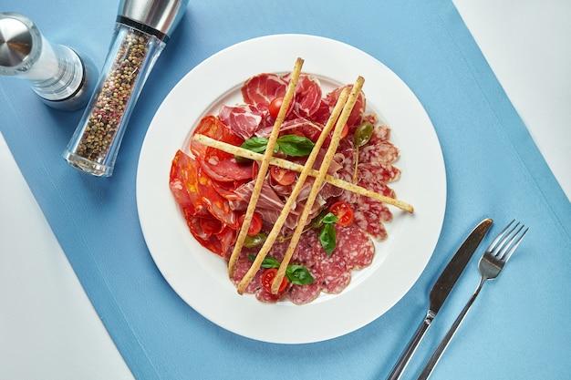 イタリアのチョリソ、サラミ、生ハムのスライス。青いテーブルクロスの白いプレートの前菜