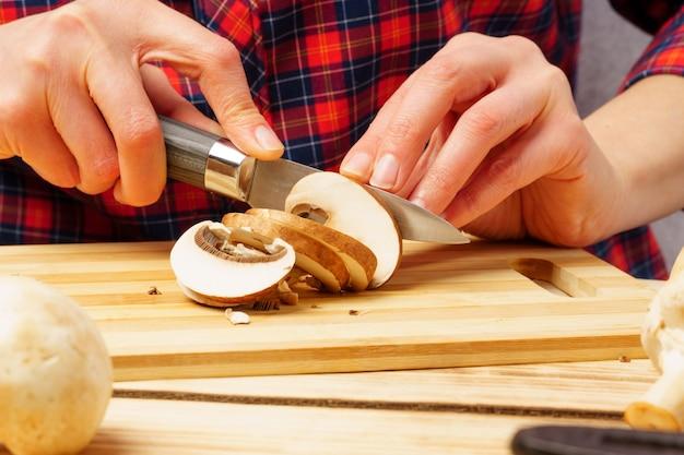 버섯 슬라이스. 커팅 보드에 champignons를 슬라이스 여성 손 클로즈업.
