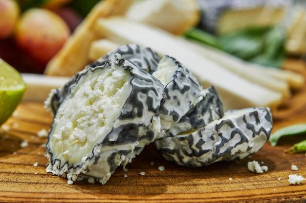 ブドウ、ライム、パイナップル、ハーブを使った木の板で、厳選されたチーズをスライスします。