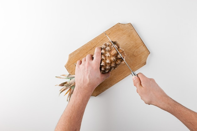 Slicing pineapple with a knife on a kitchen board