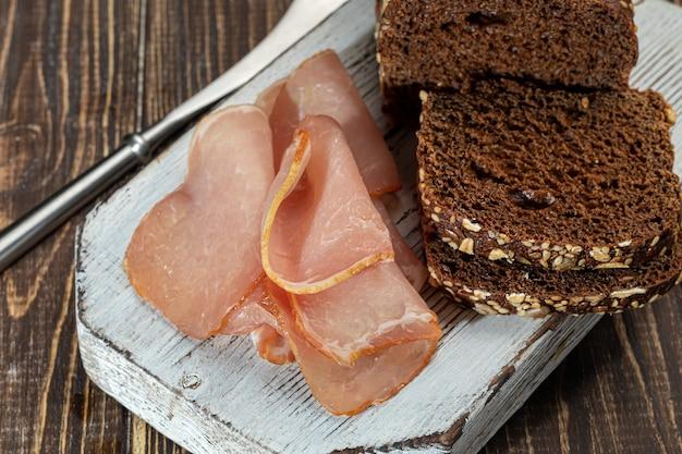 호밀 빵으로 보드에 훈제 고기를 자르십시오. 샌드위치 만들기. 나무 배경. 공간을 복사하십시오.