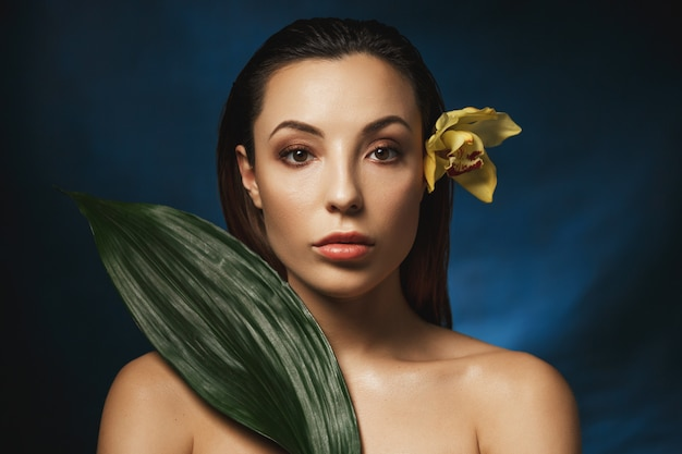 Slicked back hair hairstyle. attractive woman with flower behind ear.