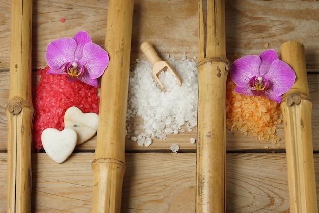 蘭の花の竹の部分が付いている木製のテーブルの上の浴室のための色とりどりの塩のスライド