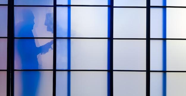 Раздвижные двери или окно для внутренней стены, состоящее из полупрозрачной бумаги на деревянной черной раме с тенью от человека. японская архитектура.