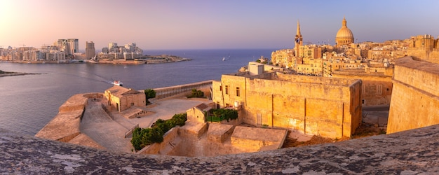 Sliema and old town of valletta with churches of our lady of mount carmel and st. paul's anglican pro-cathedral at sunset in valletta, capital city of malta