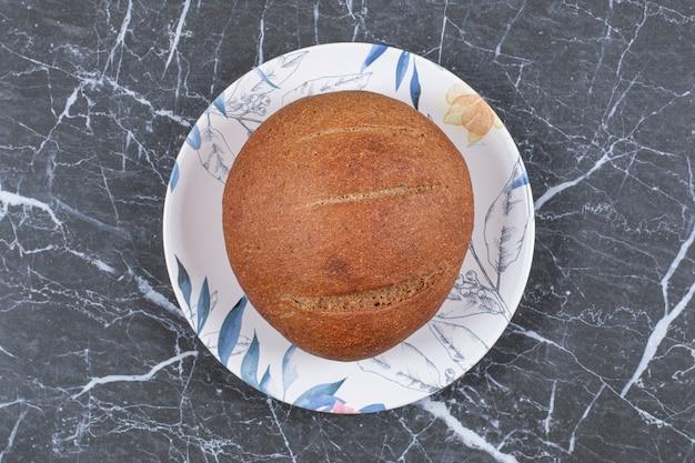 Небольшой буханка хлеба на тарелке, на мраморной поверхности