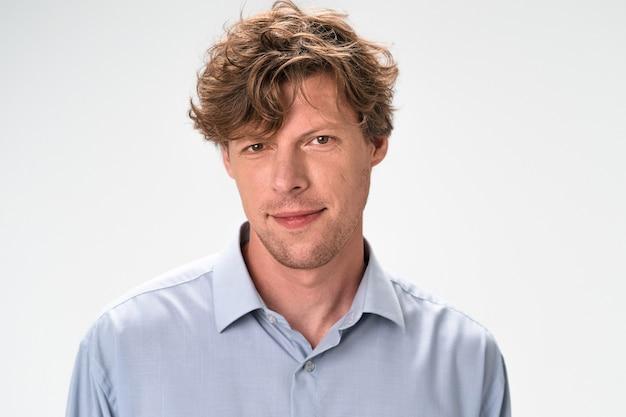 흰 벽에 고립 된 약간 웃는 남자. 붉은 곱슬 머리를 가진 엷은 갈색 눈 백인 사나이