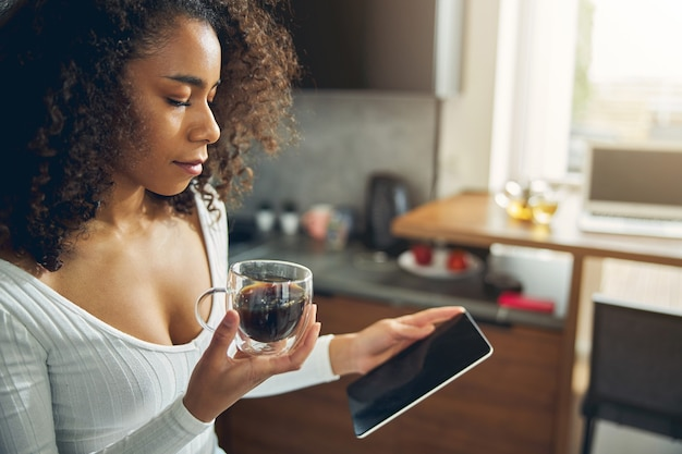 커피 한 잔을 들고 그녀의 휴대 전화와 함께 부엌에 서 슬림 아프리카 계 미국인 여성