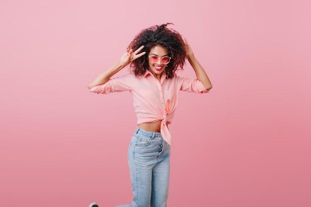 幸せを表現するヴィンテージデニムパンツのスリムなアフリカの女性モデル。ピンクの壁の近くで笑っているカジュアルな服装の魅力的な格好の良い女の子。