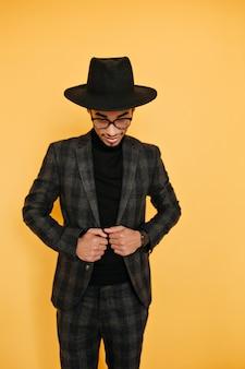 エレガントなスーツでポーズをとる大きな黒い帽子のスリムなアフリカ人。黄色の壁に隔離された灰色の服装でうれしいムラートの男の屋内写真。