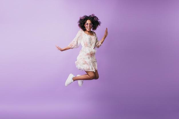 점프 하 고 웃 고 흰색 운동 화에 슬림 아프리카 여자. 기분 좋은 흑인 소녀 춤의 실내 사진.