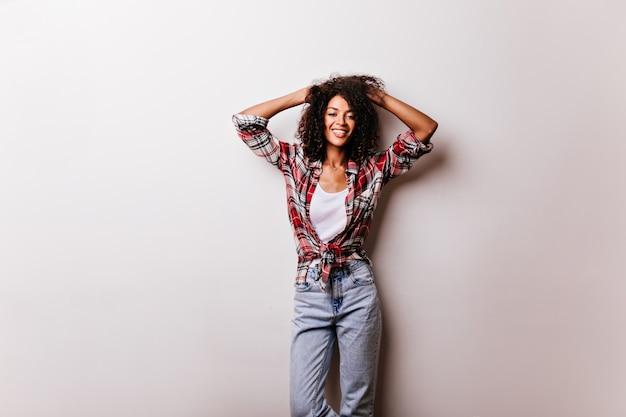 Slim ragazza africana incredibile che esprime emozioni positive su bianco. disinvolta donna che ride con i capelli ricci corti in posa in camicia a scacchi.