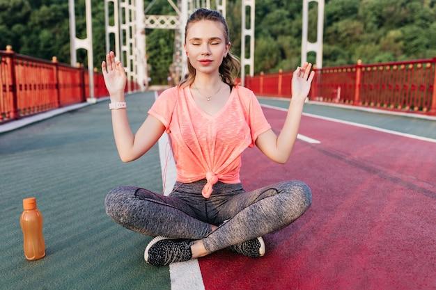 燃えがらのトラックで目を閉じて瞑想するスリムな素晴らしい女の子。夏の屋外トレーニング中に楽しんでいる壮大な若い女性。