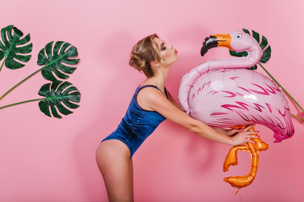 Slim amazing girl in vintage bodysuit kissing big toy bird, standing in front of pink wall. portrait of cute shapely young woman holding inflatable flamingo, posing with plants on background