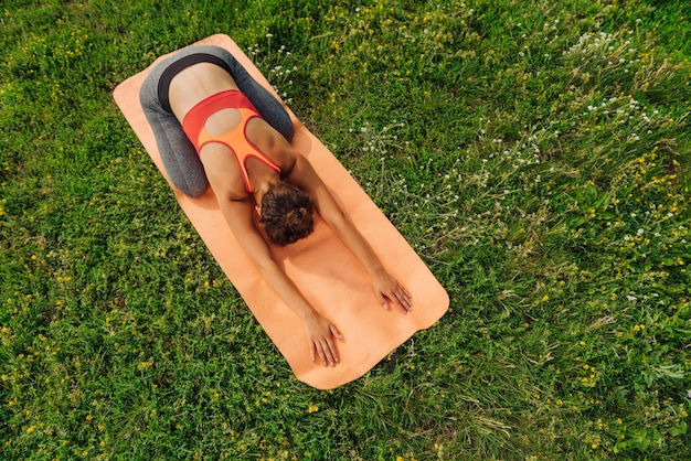 Стройная и здоровая темноволосая женщина, практикующая йогу, растягивается на ярком коврике, лежа на зеленой траве