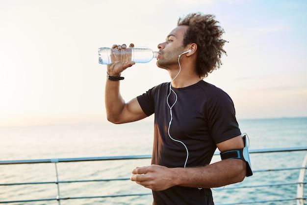 Стройный и молодой спортсмен освежается, пьет воду из пластиковой бутылки в лучах утреннего солнца. слушал свои любимые песни во время пробежки.