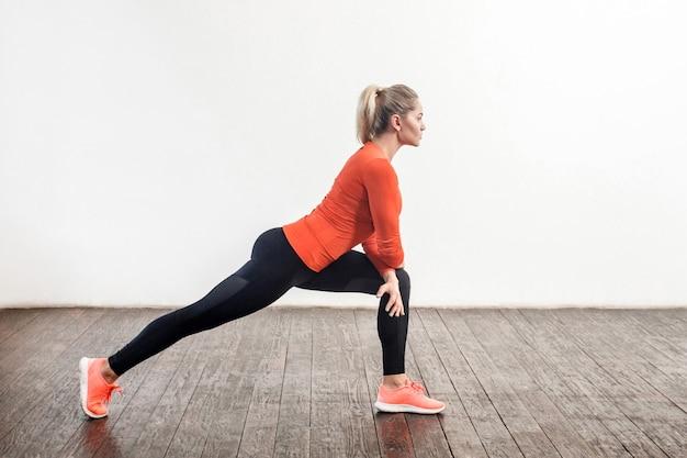 より良い柔軟性、下半身の運動のためにストレッチ脚のトレーニングをしているタイトなスポーツウェアのスリムな運動の美しい女性。健康管理、家庭でのスポーツ活動。屋内スタジオショット、側面図