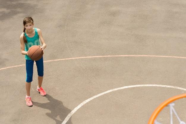 ボールを持って立っているスリムな運動の美しい若い女性のバスケットボール選手