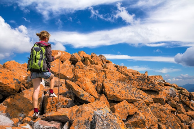 Slim athletic blond tourist hiker girl with stick and backpack climbing lit by sun high rocky mountain on bright blue sky scene. tourism, traveling, hiking and healthy lifestyle concept.