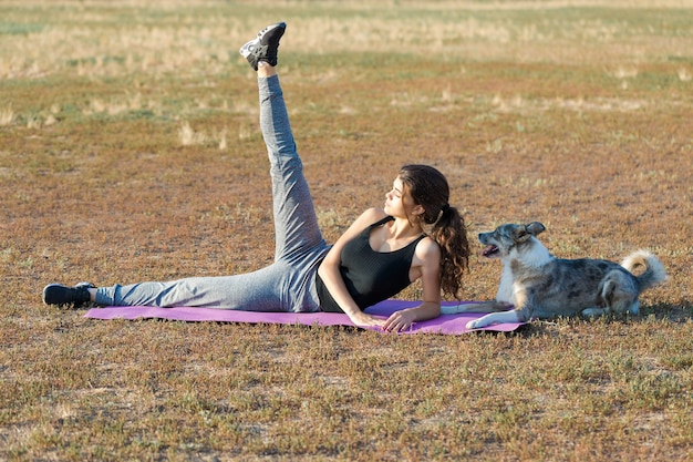 Slim athletic girl performs stretching exercises on the nature sitting on a purple yoga mat