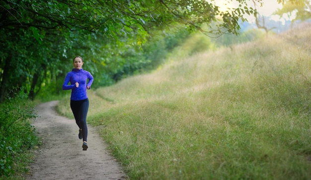 A  slim athletic jogger in a black sports leggins and and blue jacket  fast runs along the path  on the  beautiful green forest. photo show  active healthy lifestyle.