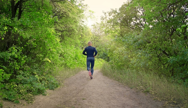 A slim  athletic jogger in a black sports leggins, shirt and sneakers runs on the  green spring forest. back view. photo shows a healthy lifestyle.