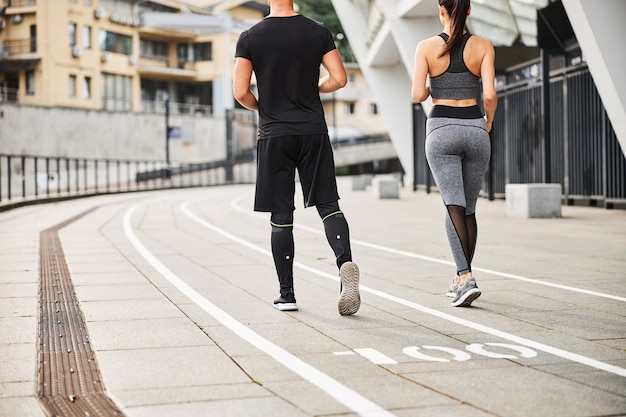 Slim athletic man and woman in sportwear are spending time actively going jogging in city centre