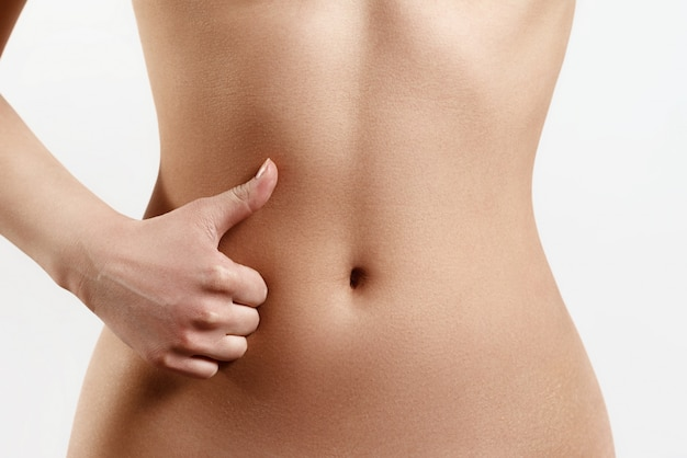 Slim, athletic waist of a young woman. the hand in the foreground shows a finger up gesture. the concept of female beauty and health, nutrition and diet, beautiful figure