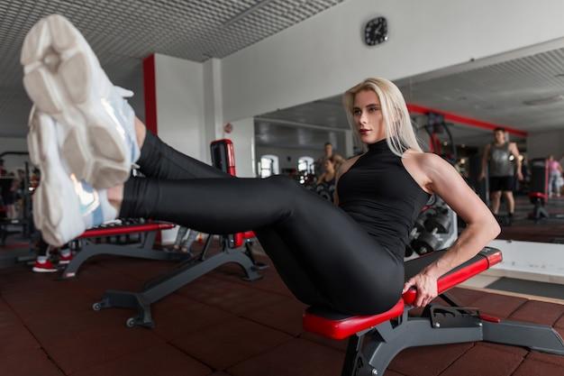Стройная спортивная молодая женщина на тренировке в тренажерном зале